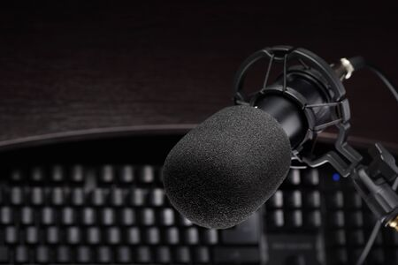Black studio condenser microphone other computer keyboard. Podcasting or internet broadcasting concept
