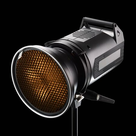 Professional photography studio flash, strobe or light with honeycomb on black background