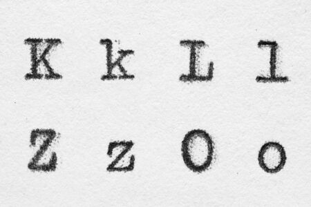 Real typewriter font alphabet with letters K, L, Z, O on white paper. Macro shot