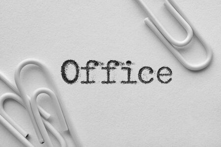 White plastic paper clips with office word printed by typewriter 스톡 콘텐츠