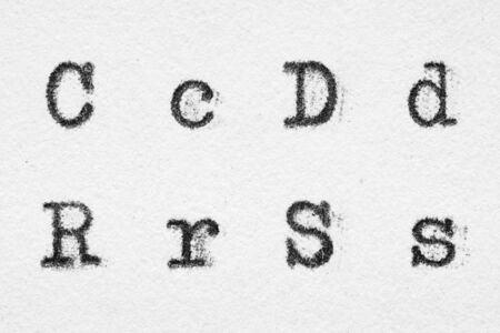 Real typewriter font alphabet with letters C, D, R, S on white paper. Macro shot