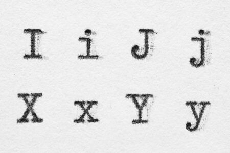 Real typewriter font alphabet with letters I, J, X, Y on white paper. Macro shot