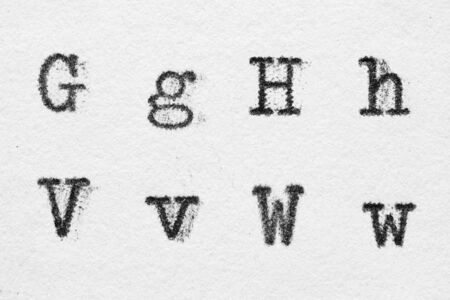 Real typewriter font alphabet with letters G, H, V, W on white paper. Macro shot