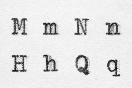 Real typewriter font alphabet with letters M, N, H, Q on white paper. Macro shot
