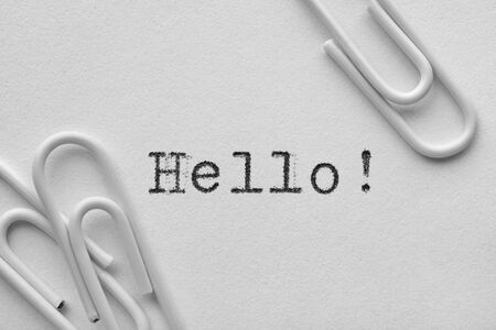 White plastic paper clips with Hello word printed by typewriter