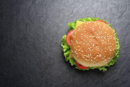 Classic cheeseburger on black slate background. Top view. Copy space