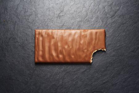 Bitten brown milk chocolate bar on black slate background. Top view
