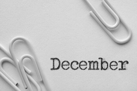 White plastic paper clips with December word printed by typewriter