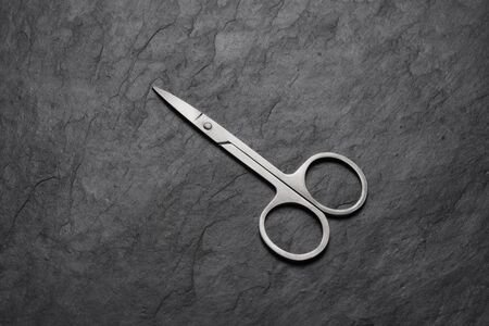 Small nail scissors for manicure on black slate background