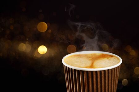 Paper cup of coffee with dark blur background as empty space. Beverages to go or take away concept