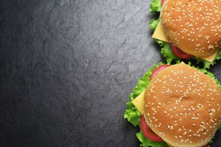 Two classic cheeseburgers on black slate background. Top view. Copy space