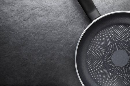 Black skillet with non-stick coated surface on dark slate background Stock Photo