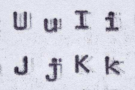 Real typewriter font alphabet with letters U, I, J, K on white paper. Macro shot