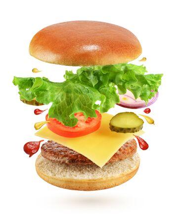 Flying Burger mit Rindfleischpastetchen, Käse, Gurken, Tomaten, Zwiebeln und Salat isoliert auf weißem Hintergrund