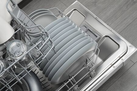 Opened domestic dishwasher with cleaned dishware in kitchen interior
