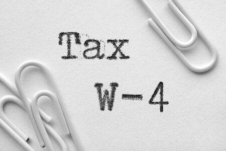 White plastic paper clips with Tax W-4 words printed by typewriter