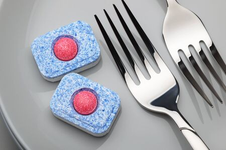 Dishwasher detergent tablet and forks on the gray dishes