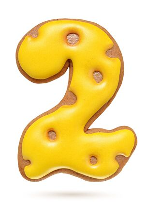 Number 2 yellow homemade gingerbread biscuit isolated at white background.