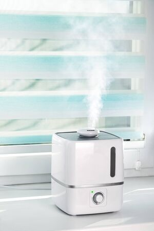 The white ultrasonic humidifier on a window of living room moistens dry air Фото со стока - 142081551