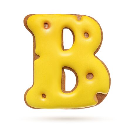 Capital letter B yellow homemade gingerbread biscuit isolated on white background.