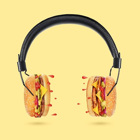 Tasty and juicy hamburger concept. Classic black headphones with burgers as a dynamics and droplets of ketchup as a sound on yellow background.