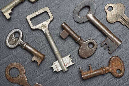 Heap of old rusty lever tumbler keys on black slate background Foto de archivo