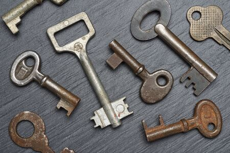 Heap of old rusty lever tumbler keys on black slate background Stockfoto