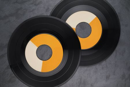 Two 7-inch single vinyl records with wide-hole on black slate background. Top view