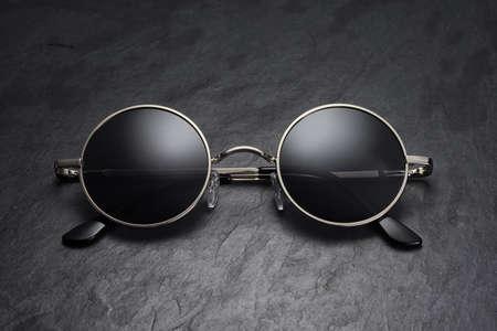 Classic round gray gun metal sunglasses on on black slate background