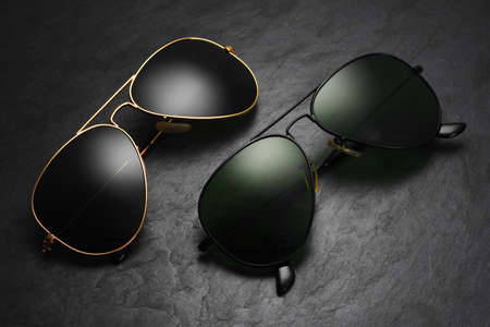 Classic old fashion aviator sunglasses on black slate background. Top view