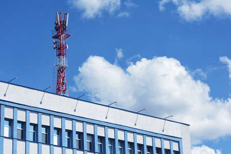 Telecom cellular base station tower on the building with blue sky and clouds