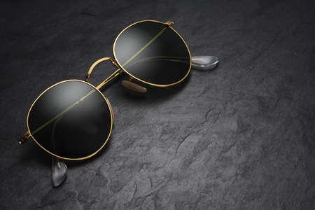 Gold frame round black sunglasses on black slate background with copy space. Stockfoto