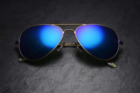 Blue mirror aviator sunglasses with golden frame on black slate background Stockfoto