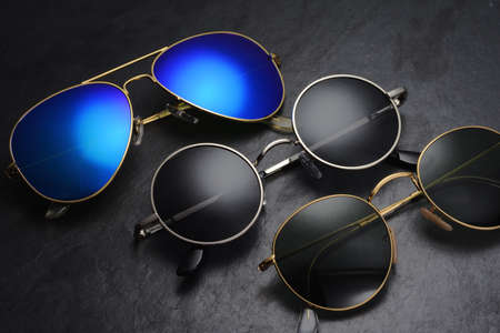 Set of different sunglasses arranged in a row on black slate background