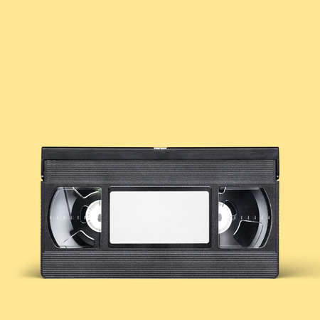 Black VHS video tape cassette with blank label on yellow background