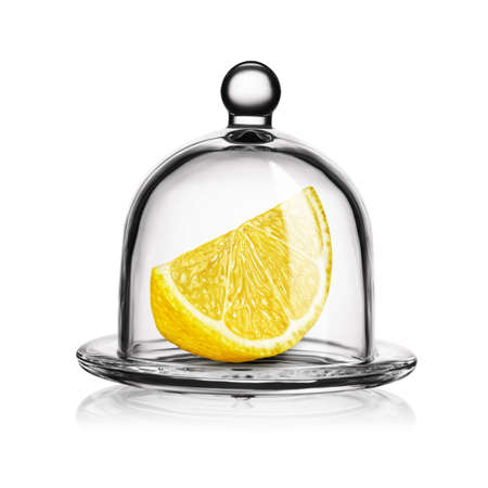 Slice of yellow lemon in glass bell jar isolated on white background.