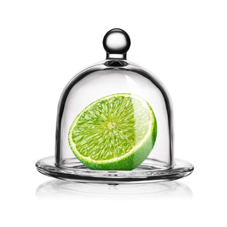 Slice of green lime in glass bell jar isolated on white background.