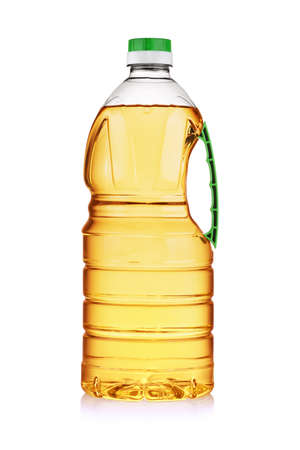 Plastic bottle with green handle of yellow vegetable cooking oil isolated on white background.