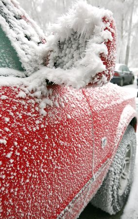 Red car with outside mirror covered of icing