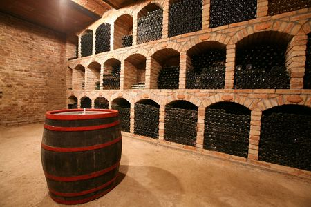 Vintage wine bottles stacked in the old cellar of the winery Stock Photo