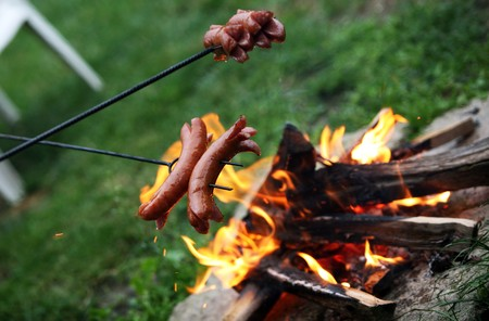 Roasting sausages on campfire in the garden photo