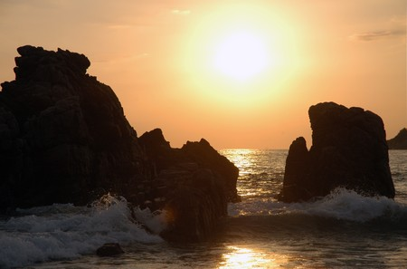 Silhouette of monument during sunset over the beach of Puerto Escondido photo