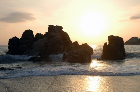 Silhouette of monument during sunset over the beach of Puerto Escondido Stock Photo