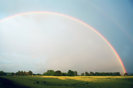 Rainbow on  blue sky over the rural landscape Stock Photo
