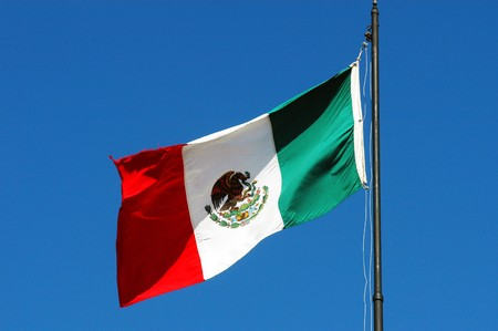 Mexican national flag waving on blue sky Stock Photo