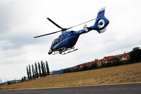 retrieve: Blue and silver police helicopter flying above