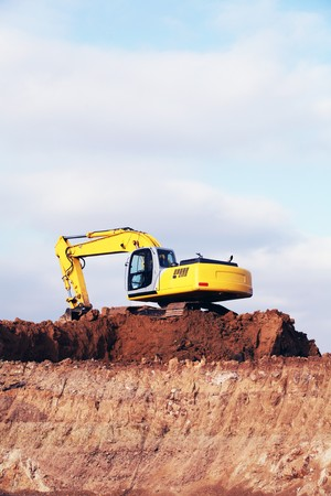 Yellow heavy earth mover digging the soil photo