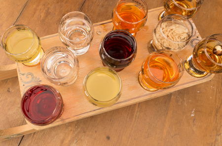 kinds: A group of glasses of various alcohol stacked on wooden board