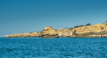 A view of cliff on the Algarve coast from a boat sailing on the sea in Portugal, 2016