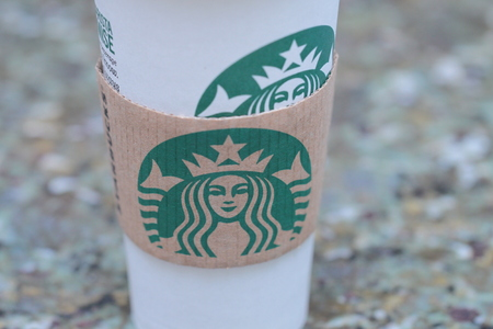 Venti Starbucks cup and sleeve on light granite background Editorial